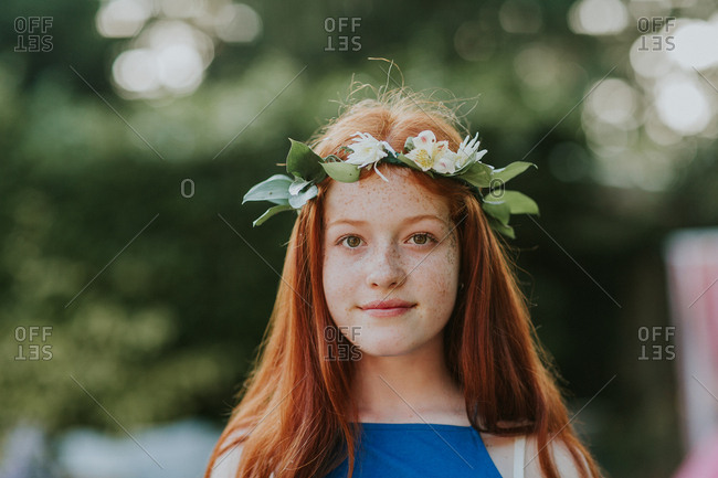 Young redhead teenager wearing floral crown