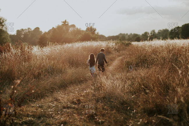 Two siblings walking together in rural field