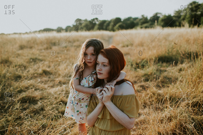 Little girl wrapping her arms around teen sister in a field