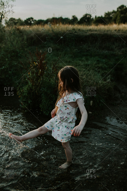 Young girl splashing in a creek