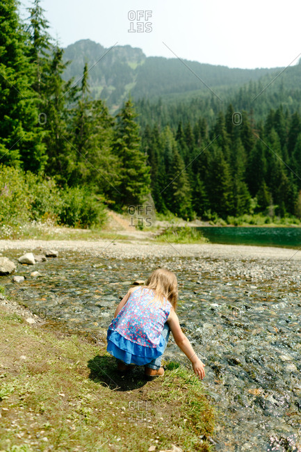 Little girl touching water in Gold Creek Pond in Washington