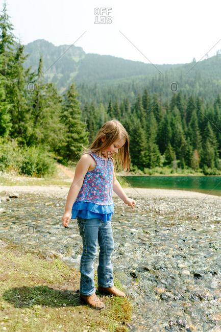 Little girl standing on edge of water in Gold Creek Pond in Washington