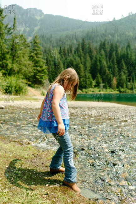 Little girl dipping foot into water in Gold Creek Pond in Washington