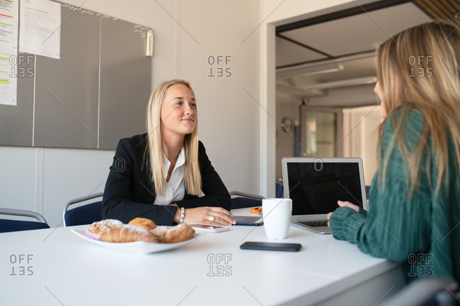 Two young businesswomen in an office eating pastries