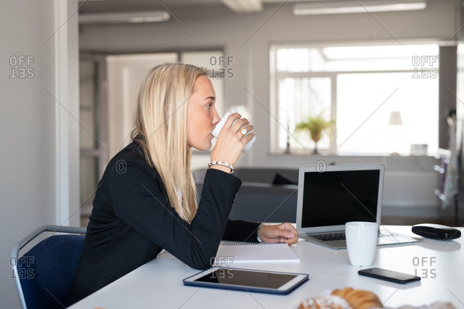 Young blonde businesswoman drinking coffee in an office