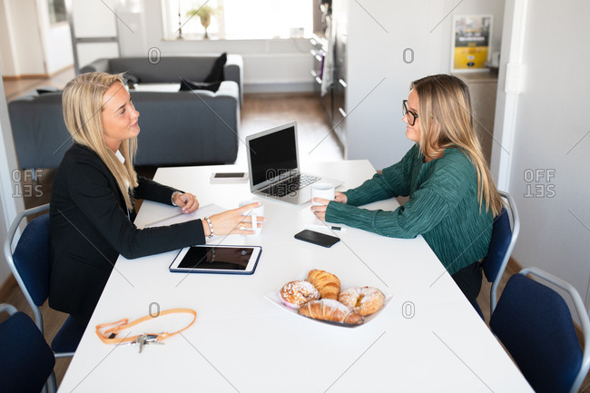 Young businesswomen in an office eating pastries and drinking coffee