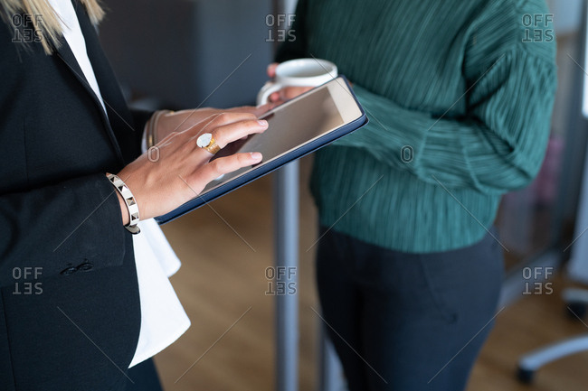 Close up of businesswomen in an office working on tablet