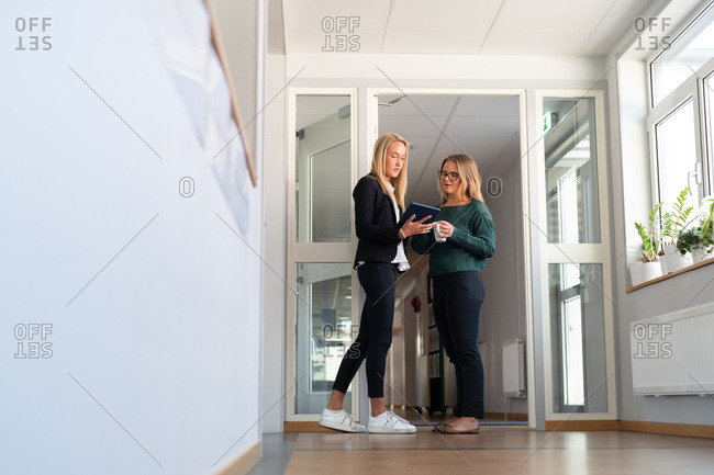 Two businesswomen standing in an office working on tablet