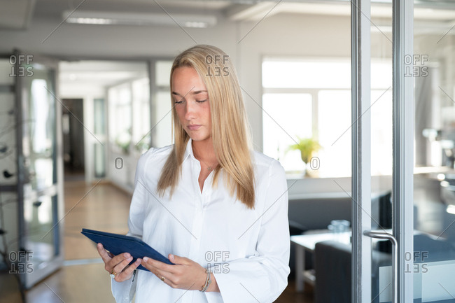 Blonde businesswoman working on tablet in an office