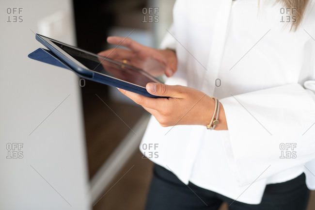 Hands of a businesswoman holding tablet in an office