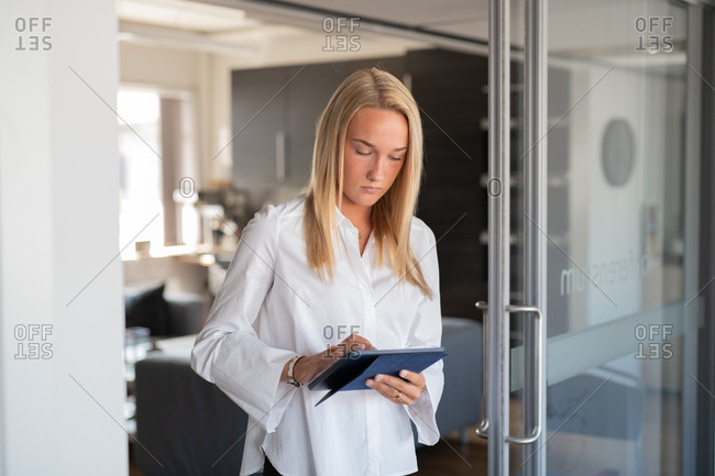 Young blonde businesswoman working on tablet in an office
