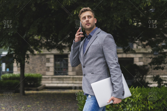 Young Businessman on the Phone Walking Down the Streets