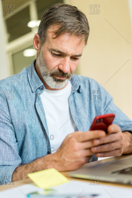Man browsing smartphone in office