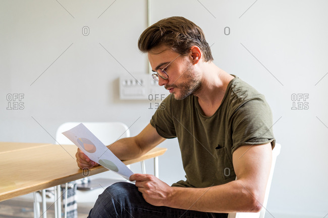 Side view of male in glasses sitting in office holding document and attentively considering it