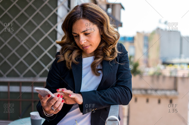 Cheerful business woman browsing smartphone