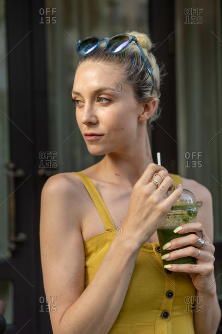 Attractive tanned female with sunglasses in yellow dress with thin straps holding cup with green healthy organic beverage with straw and looking away