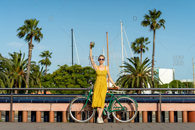 Woman in summer clothes leaning on bike