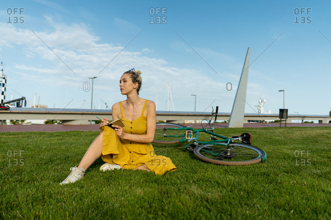 Elegant woman in flowing yellow dress and sneakers sitting on lawn with bike lying behind and writing with pen in small notebook looking away