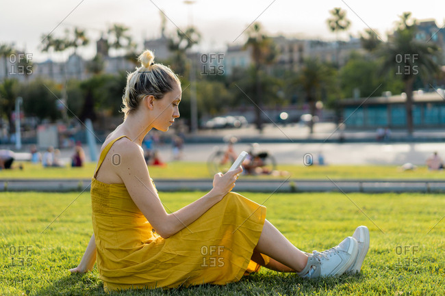 Side view of attractive blond female with fastened hair in long yellow summer dress and sneakers sitting relaxed on lawn with mobile phone leaning on arm