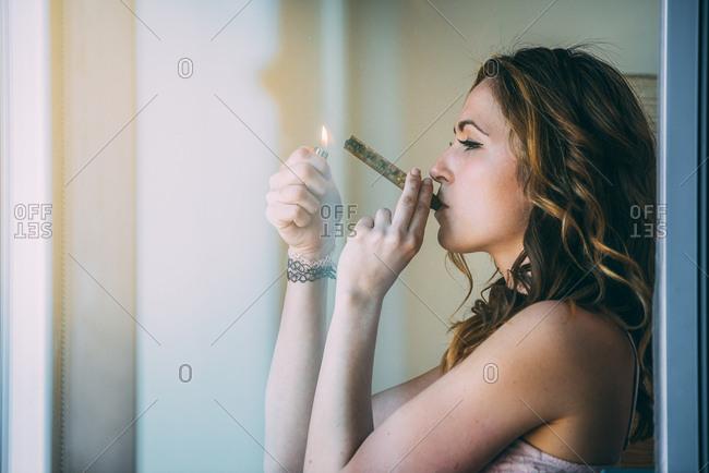 Woman smoking marijuana in a glass blunt