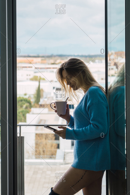 Sensual girl in sweater holding cup of coffee and surfing smartphone standing in doorway of balcony.