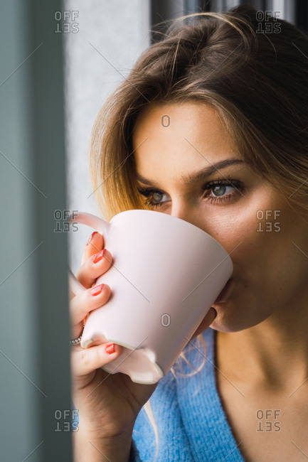 Close-up of pensive beautiful blond woman drinking refreshing coffee from pink mug looking away.