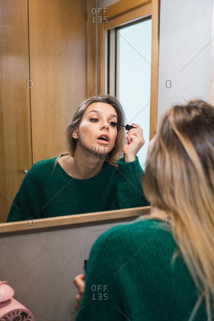 Reflection of focused woman in green sweater doing makeup in front of mirror and applying mascara.