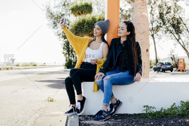 Cheerful young women sitting and taking selfie on street together.
