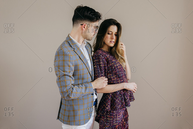 Handsome man and pretty woman in stylish clothes standing at beige wall.