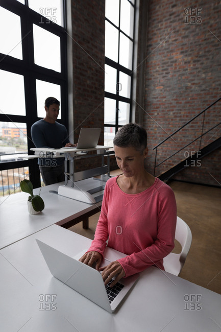 Attentive female executive using laptop in office