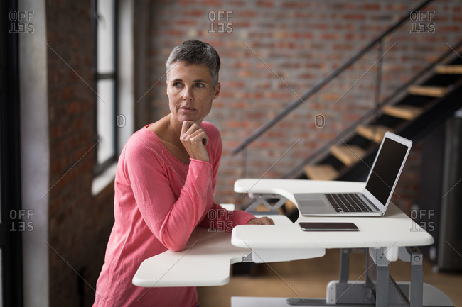 Thoughtful female executive using laptop in office