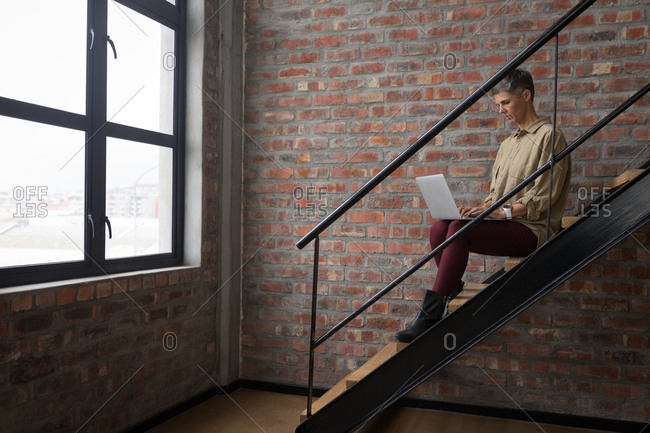 Businesswoman using laptop on stairs at office