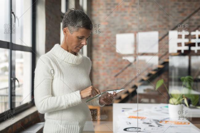Businesswoman using glass digital tablet in office
