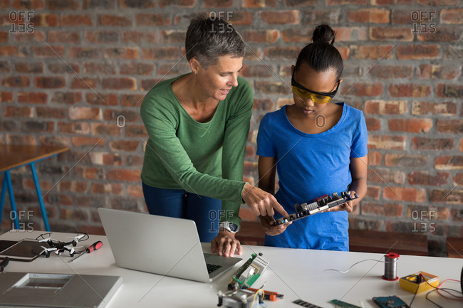 Mother explaining her daughter about circuit board in office