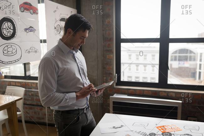 Attentive businessman using digital tablet in office