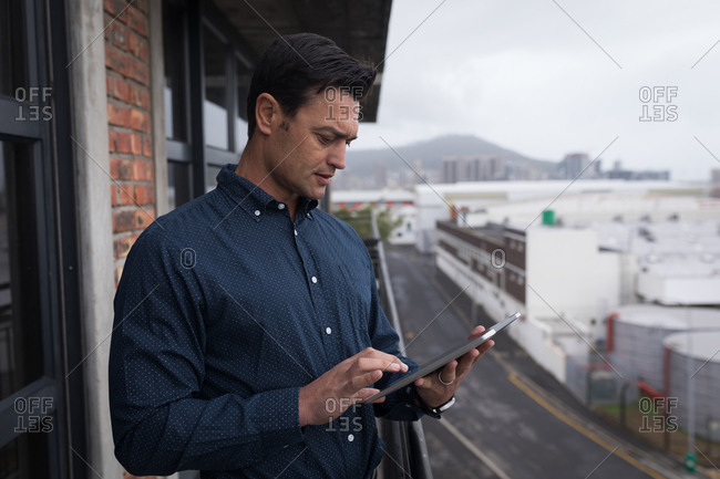 Businessman using digital tablet in balcony at office