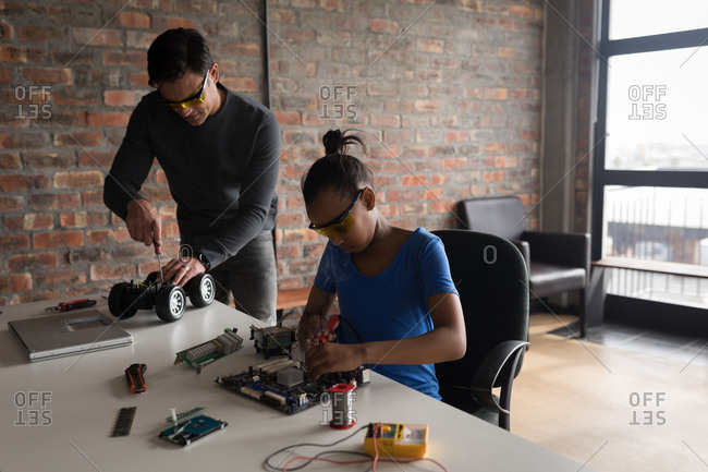 Father and daughter repairing electric model car and circuit board in office