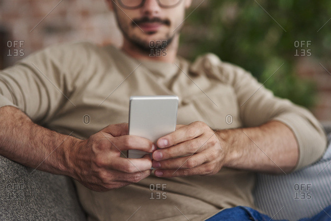 Man sitting on couch text messaging- partial view