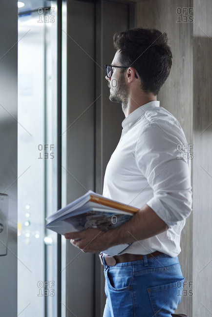 Businessman with magazines entering the elevator