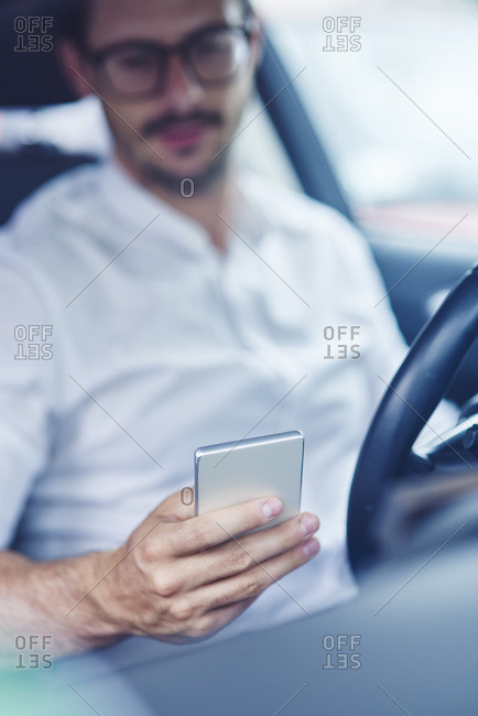 Hand of businessman sitting in car holding cell phone