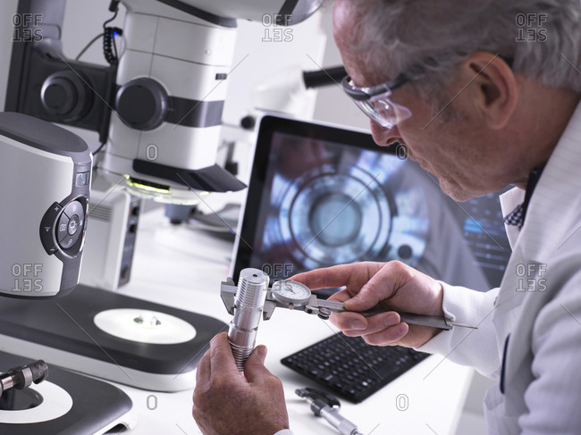 Engineer using a dial caliper and a 3d stereo microscope for quality control in the manufacturing of engineering components for industry