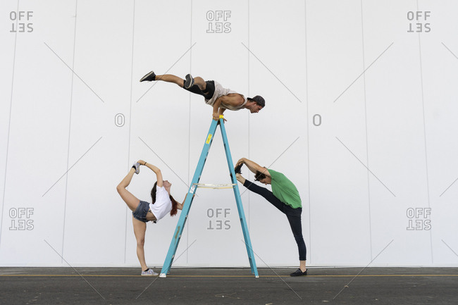 Three acrobats doing tricks on a ladder