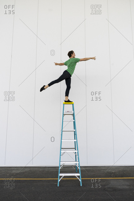 Acrobat balancing on ladder