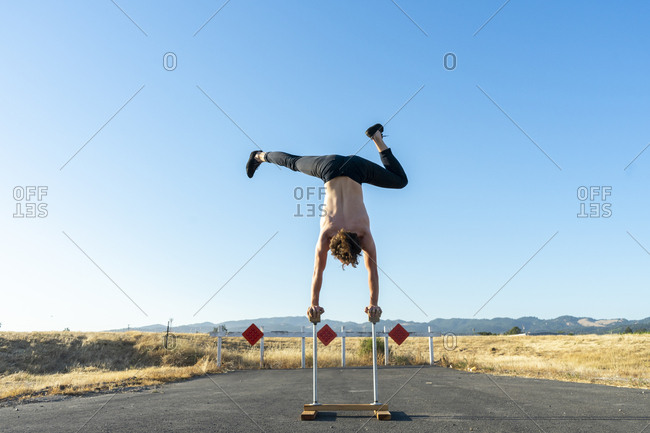 Acrobat doing handstand on handstand canes