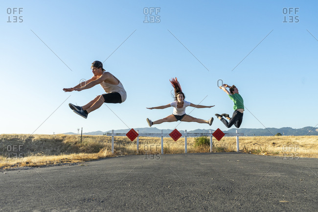 Three acrobats jumping mid-air