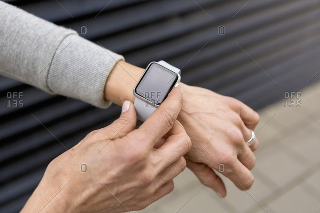 Woman's hand adjusting settings of smartwatch- close-up
