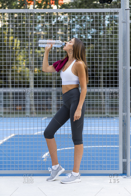Sportive young woman standing at sports field drinking water from bottle