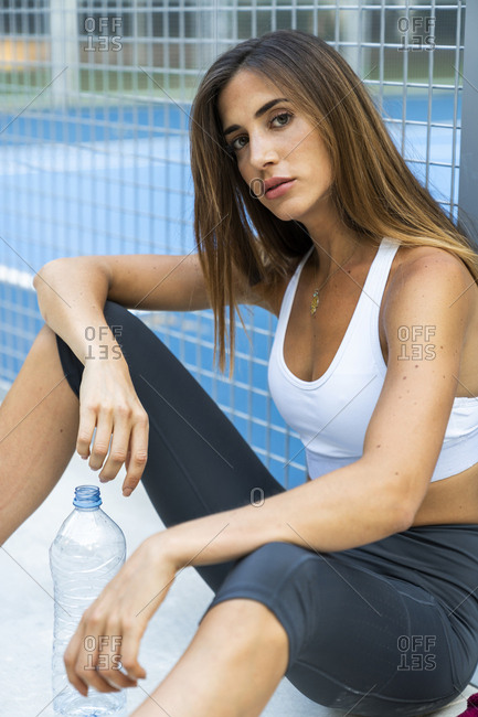 Portrait of sportive young woman sitting at sports field with water bottle