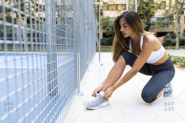 Sportive young woman tying her shoes before workout