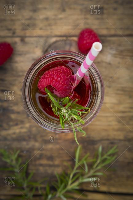 Glass bottle of homemade raspberry lemonade flavored with rosemary